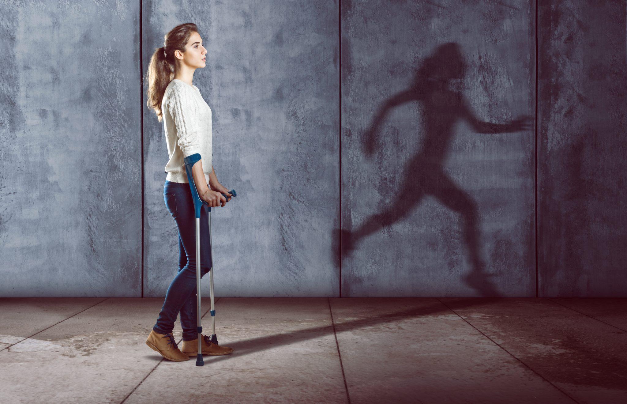 Kobieta idzie o kulach, w tle jej cień jest w pozycji biegnącej