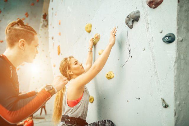 Kobieta rozpoczyna wspinaczkę na ściankę