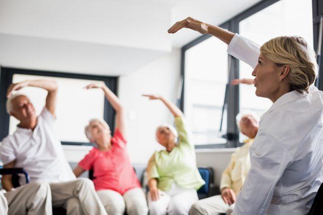 Grupa seniorów uprawia ćwiczenia