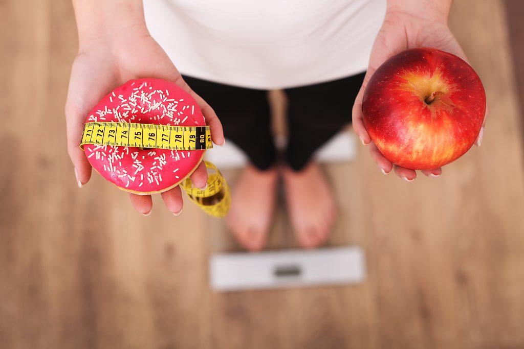 Kobieta stoi na wadze, w jednym ręku trzyma jabłko, w drugim pączka i miarkę