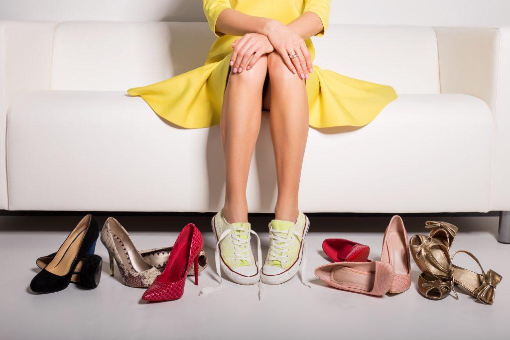 Kobieta siedzi na sofie, obok niej leży kilka par butów