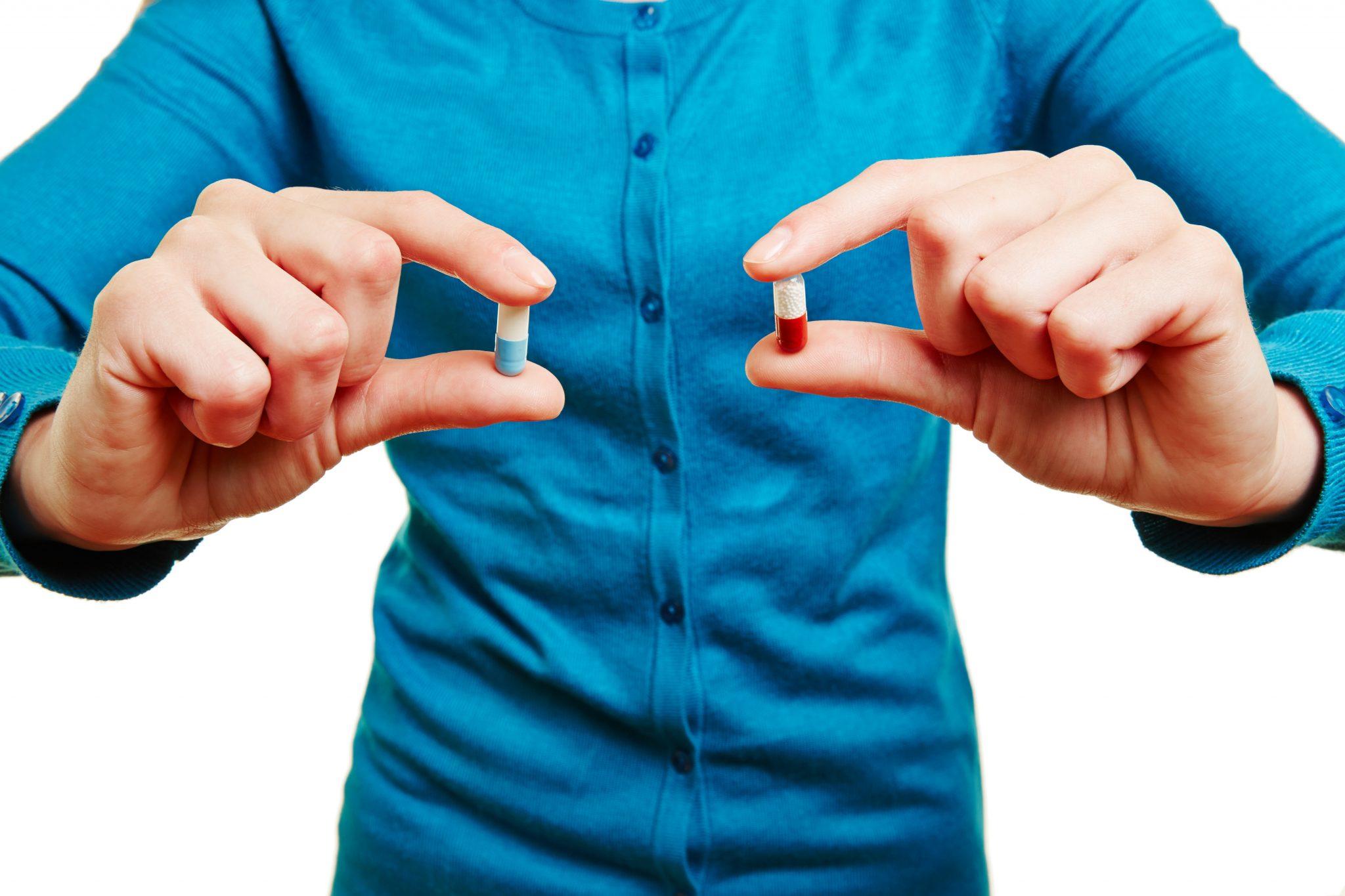 Mężczyzna trzyma w rękach dwie pigułki, niebieską i czerwoną