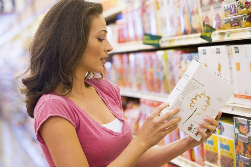 Kobieta w sklepie czyta skład na opakowaniu