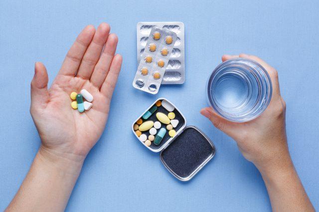 Osoba trzyma w jednej ręce tabletki, w drugiej wodę do ich popicia
