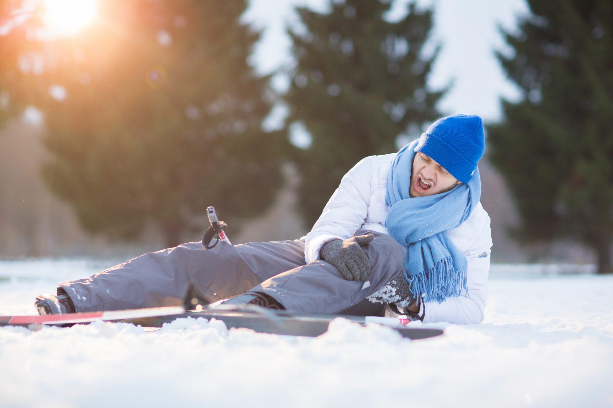 Narciarz leży na śniegu i krzyczy z bólu i trzyma ręce na bolącym kolanie