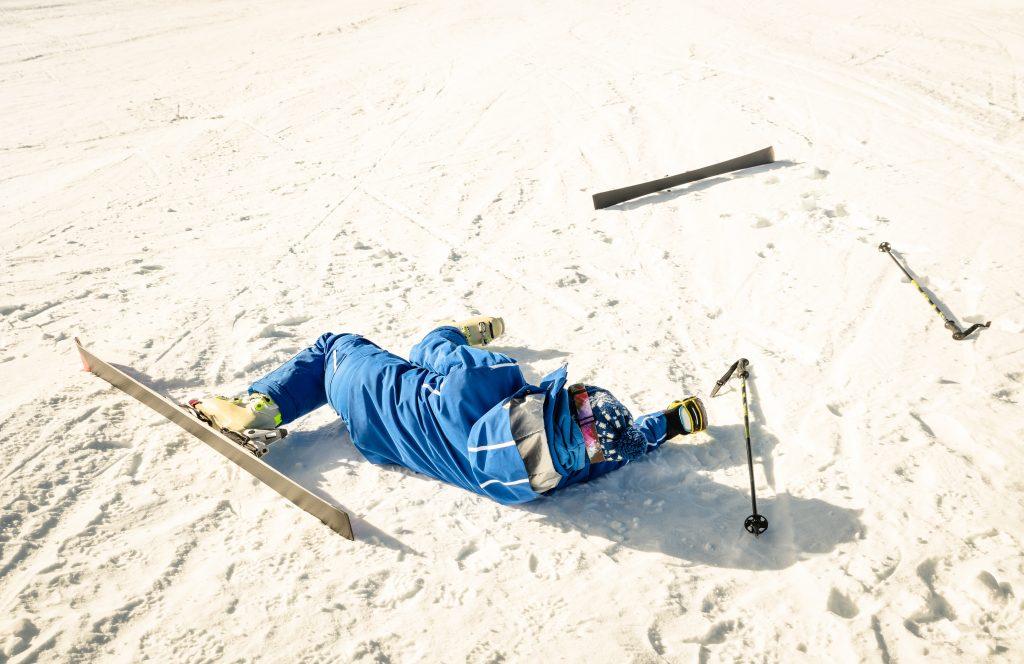 Narciarz po upadku leży w śniegu, jedna z nart leży kawałek od niego