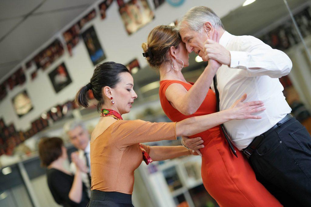 Starszy mężczyzna tańczy z kobietą pod okiem profesjonalnej trenerki