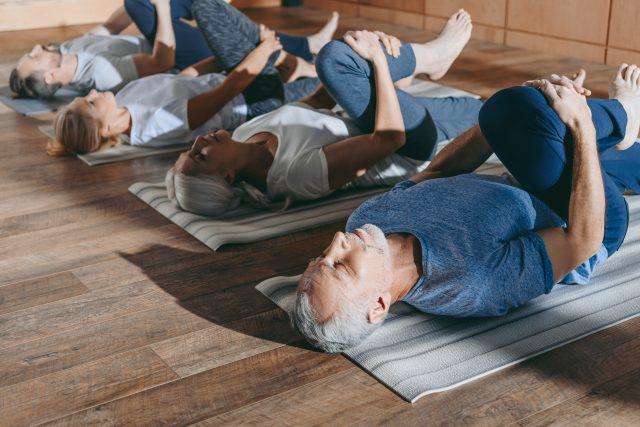 Grupa seniorów wykonuje ćwiczenia rozciągające z jogi