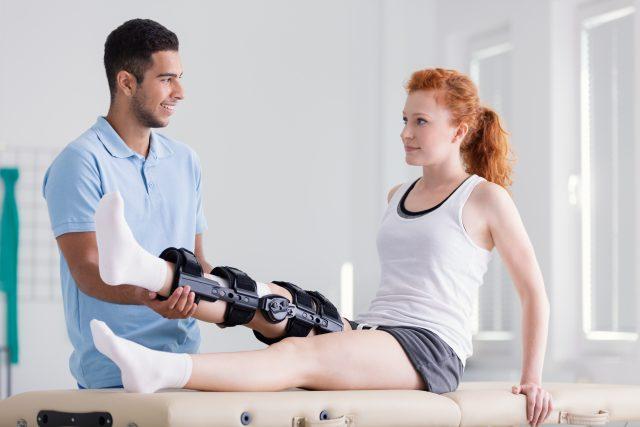 Młoda kobieta w usztywnieniu w trakcje rehabilitacji u fizjoterapeuty