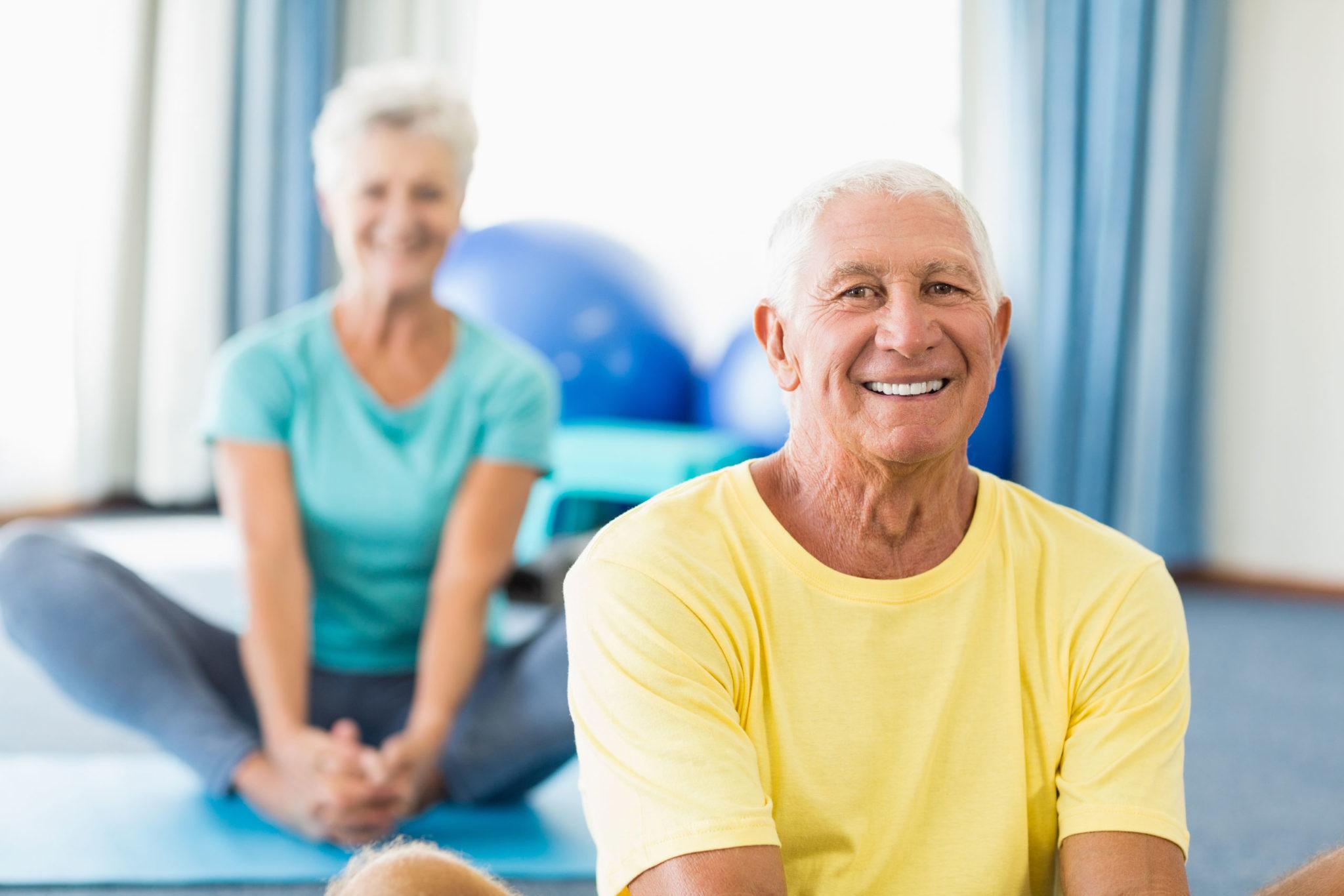 Dwójka seniorów wykonuje ćwiczenia rozciągające