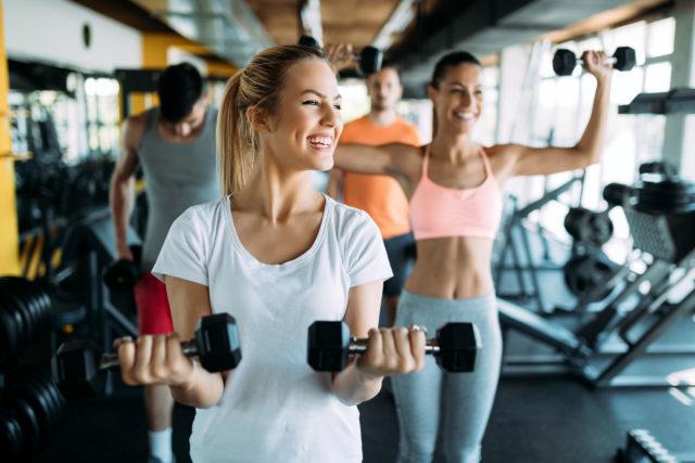 Grupa osób ćwiczy na siłowni ze sztangami