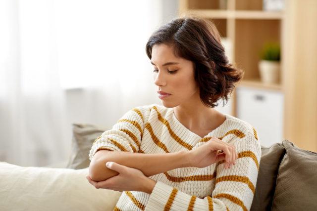 Kobieta trzymająca sięza bolący łokieć